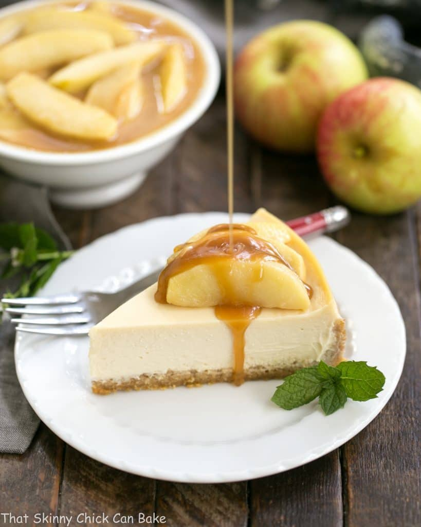 Caramel pouring over a slice of Easy Sour Cream Cheesecake with Caramel Apples