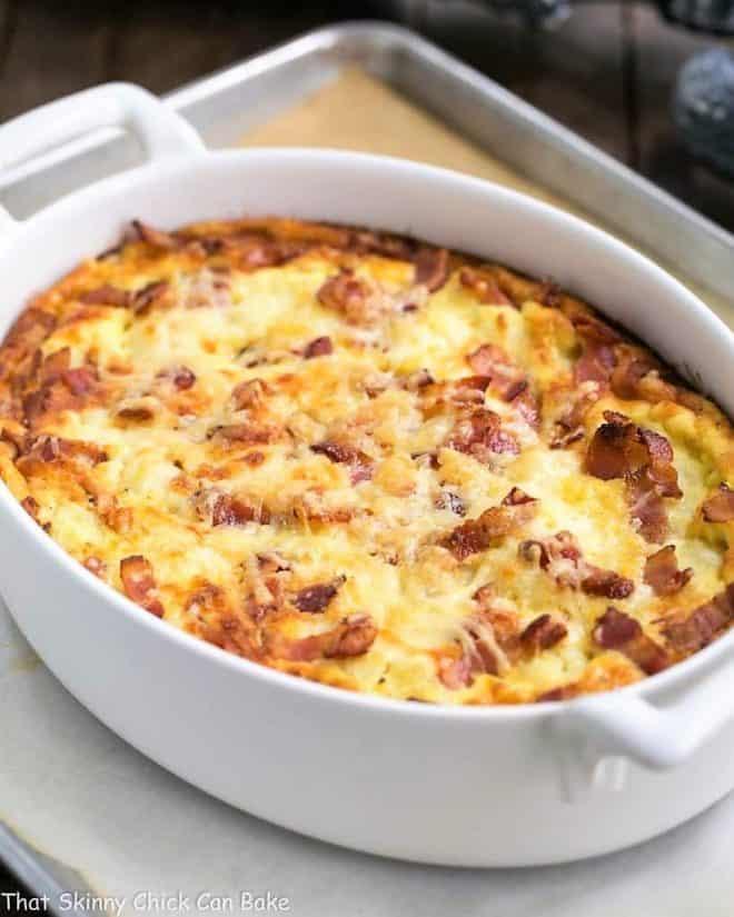 Cauliflower bacon gratin in a white baking dish on a sheet pan