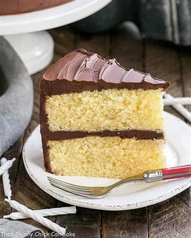 Classic Yellow Butter Cake with chocolate Icing on a white plate with a red handled fork