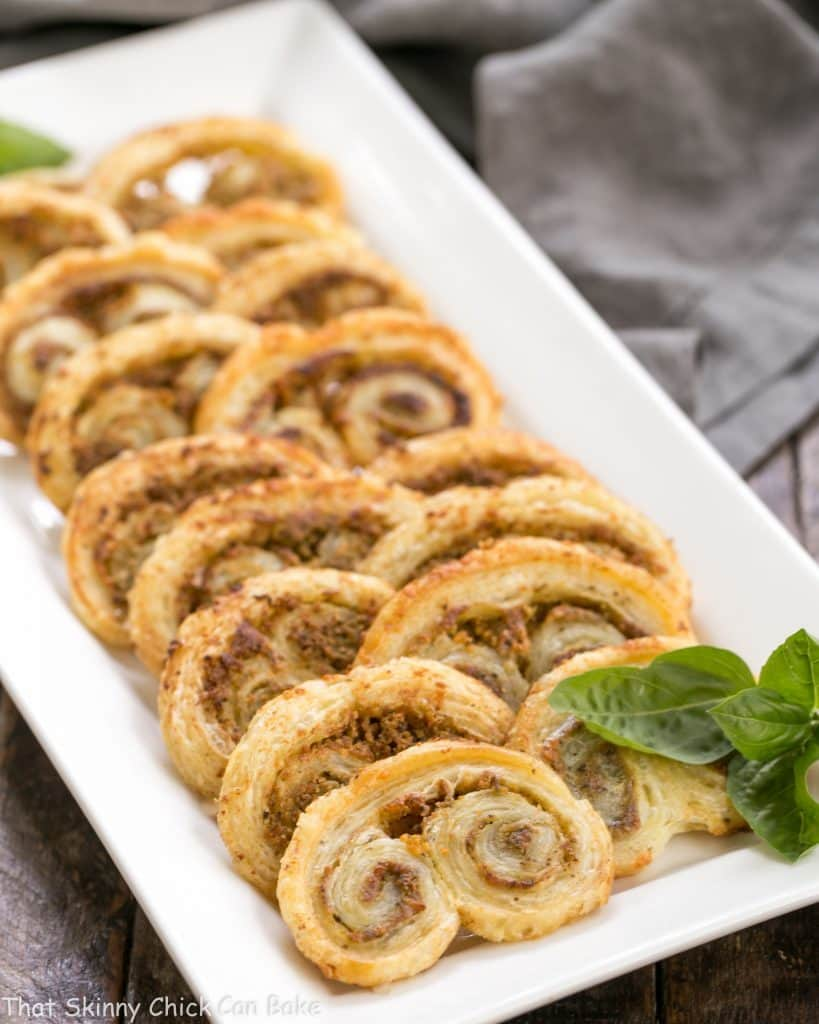 Easy Pesto Palmiers lined up on a white ceramic tray with sprigs of basil