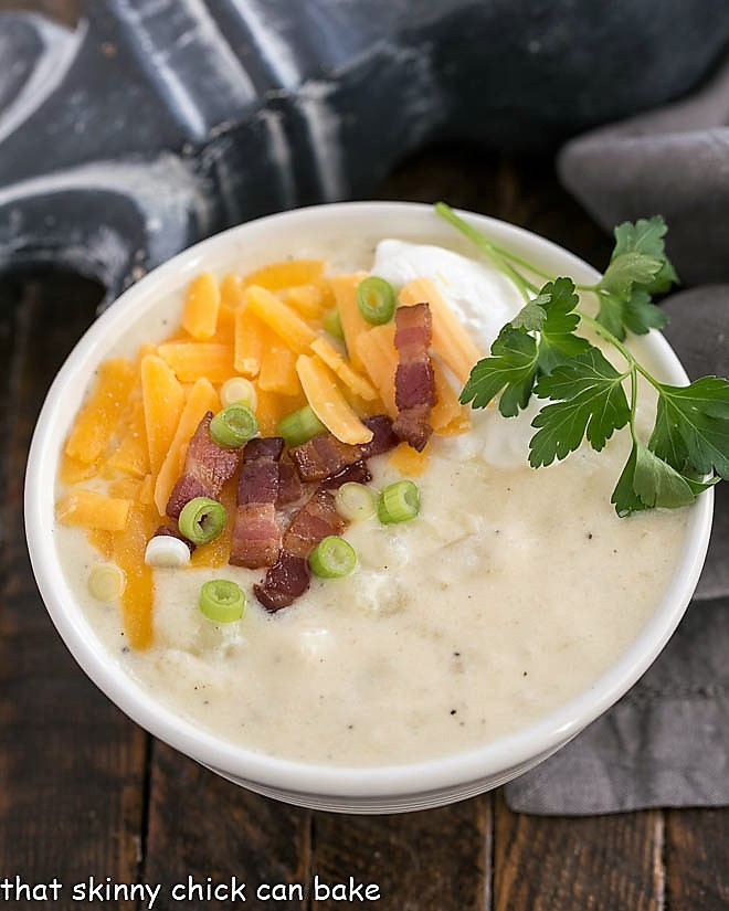 Loaded Baked Potato Soup in a white bowl with cheese and bacon garnish