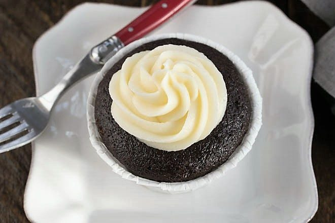 Overhead view of a blackbottom cupcake on a square white plate with a red handled fork