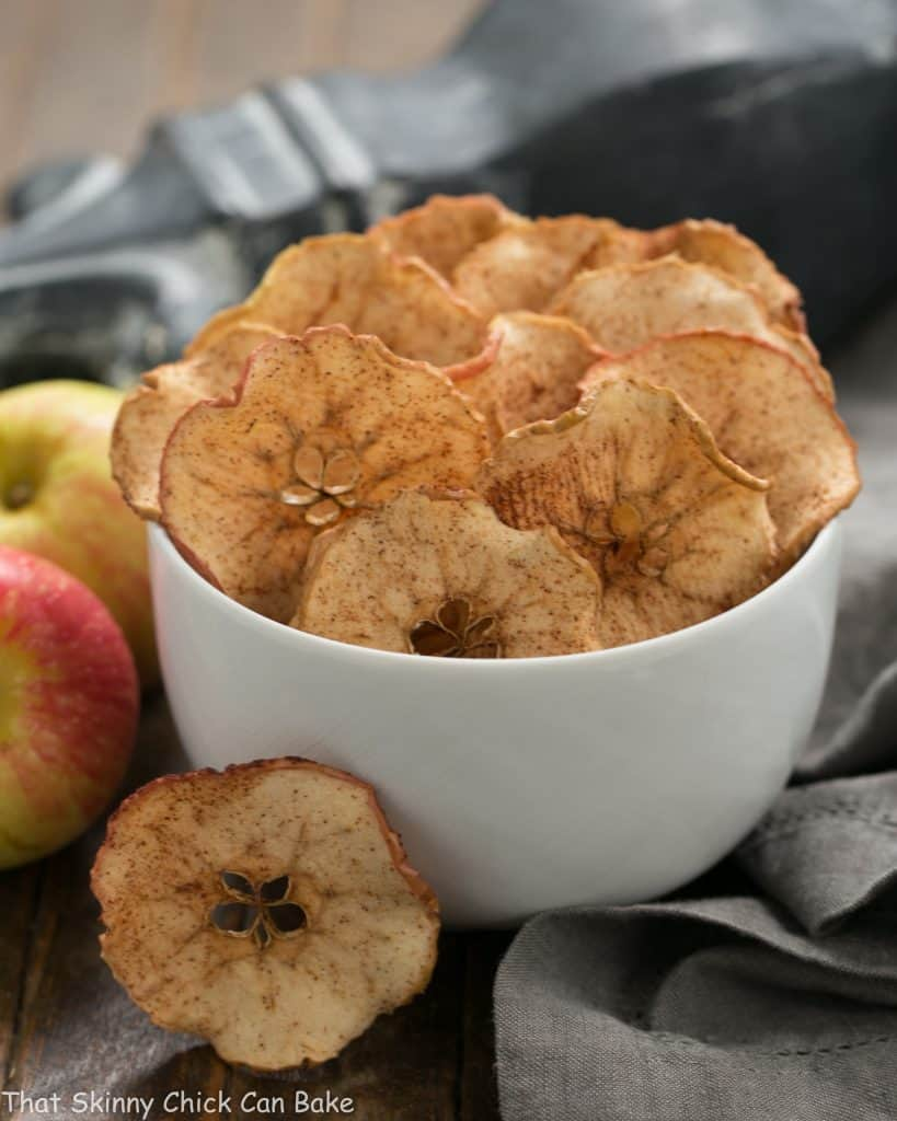 Cinnamon Apple Chips in a white ceramic bowl next to fresh apples