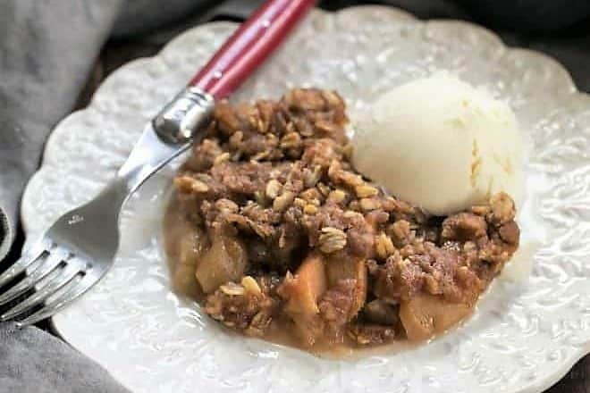 A decorative plate with slow cooker apple crisp and a scoop of vanilla ice cream