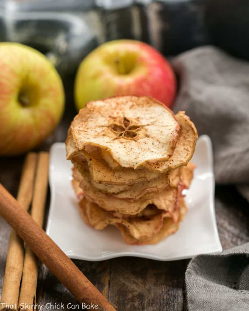 A stack of Cinnamon Apple Chips on a square white plate with fresh apples and cinnamon sticks