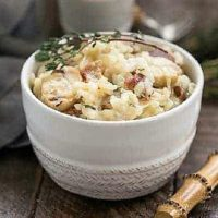 A bowl of bacon mushroom risotto in a white bowl