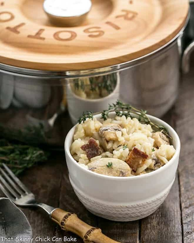 Bacon Mushroom Risotto with Caramelized Onions in a small white bowl with a garnish of thyme