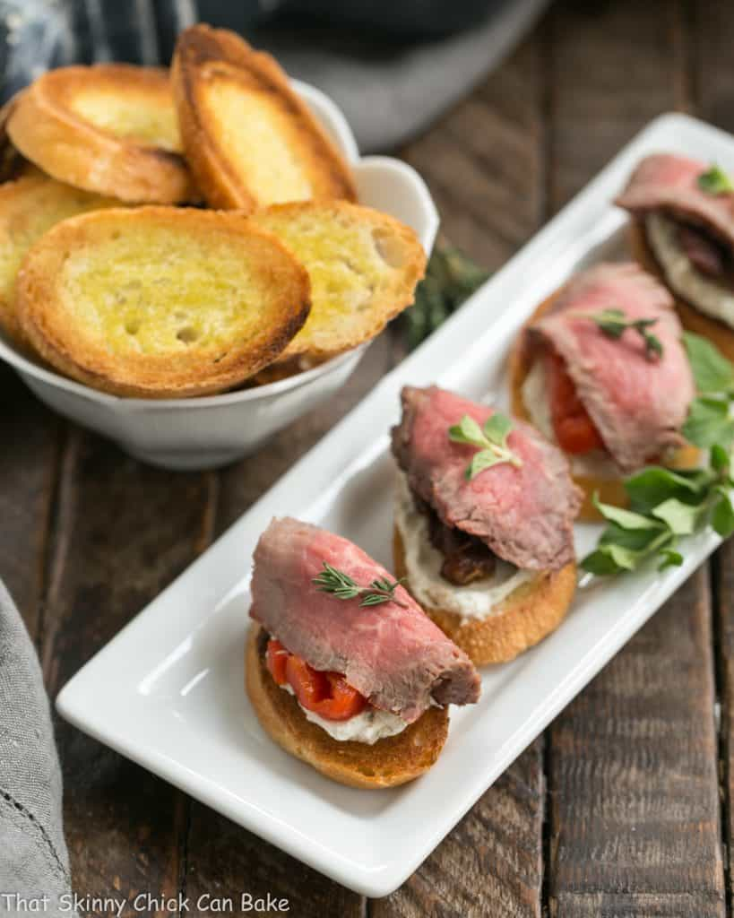 Beef Crostini with Blue Cheese Spread on a narrow white tray viewed from above