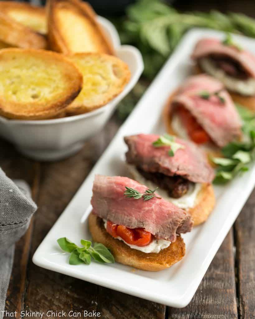 Beef Crostini with Blue Cheese Spread lined up on a white platter