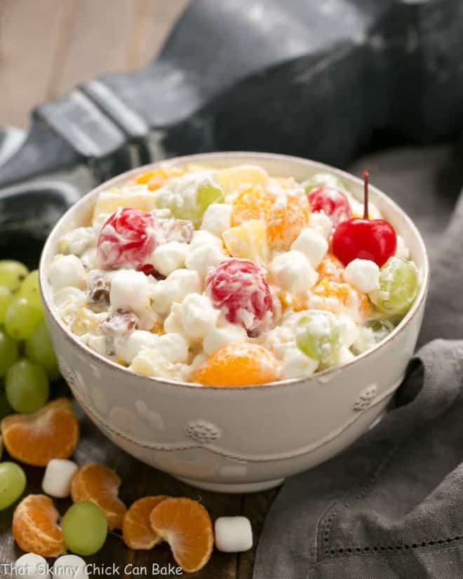 The Best Ambrosia Salad  in a white serving bowl surrounded by fruit and marshmallows