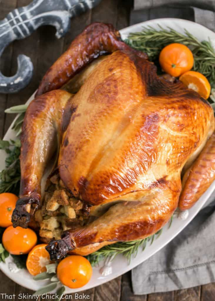 Honey Brined Turkey on a white platter garnished with herbs and oranges