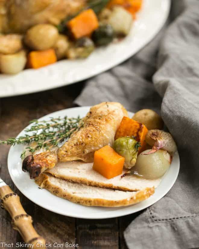 Sheet Pan Chicken with Roasted Fall Vegetables on a platter with a serving on a white plate in the foreground