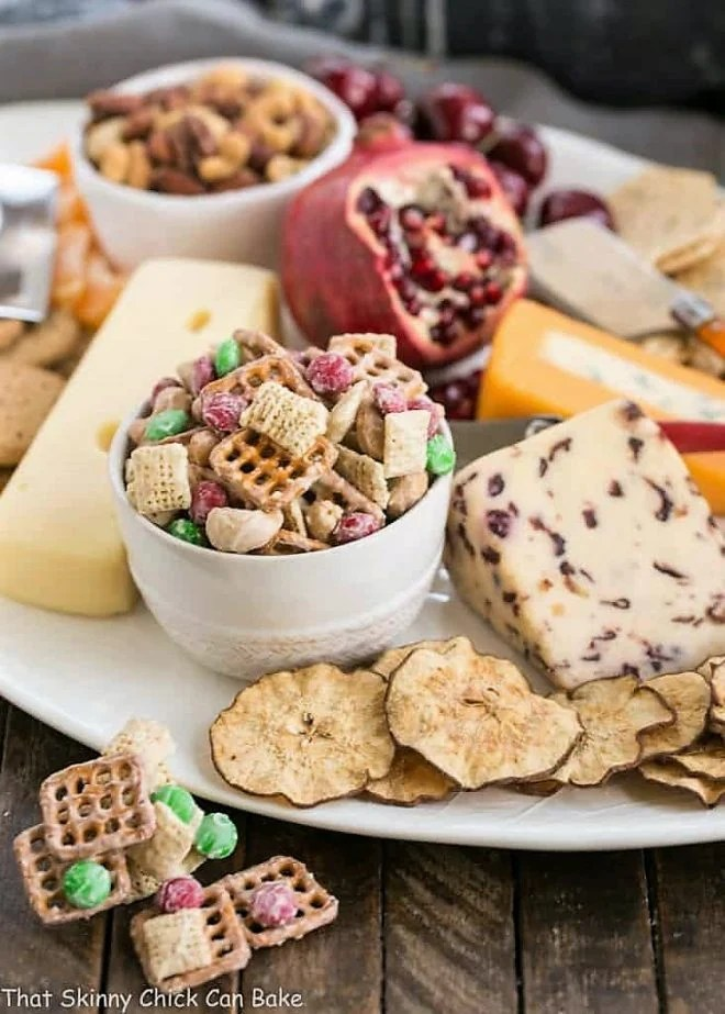 a bowl of snack mix sitting on a cheese appetizers appetizer