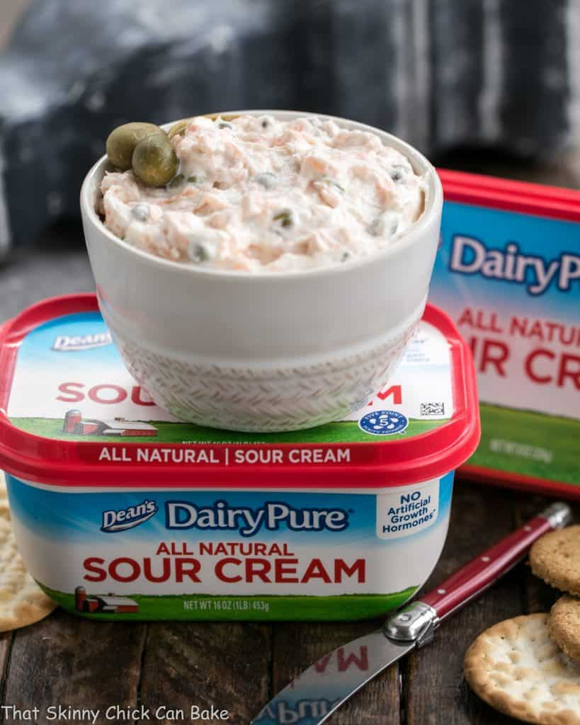 a bowl of Smoked Salmon Dip with Capers sitting on top of a container of DairyPure brand sour cream