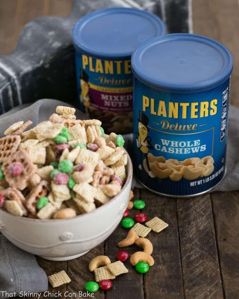 a bowl of party mix next to cans of Planter's roasted nuts