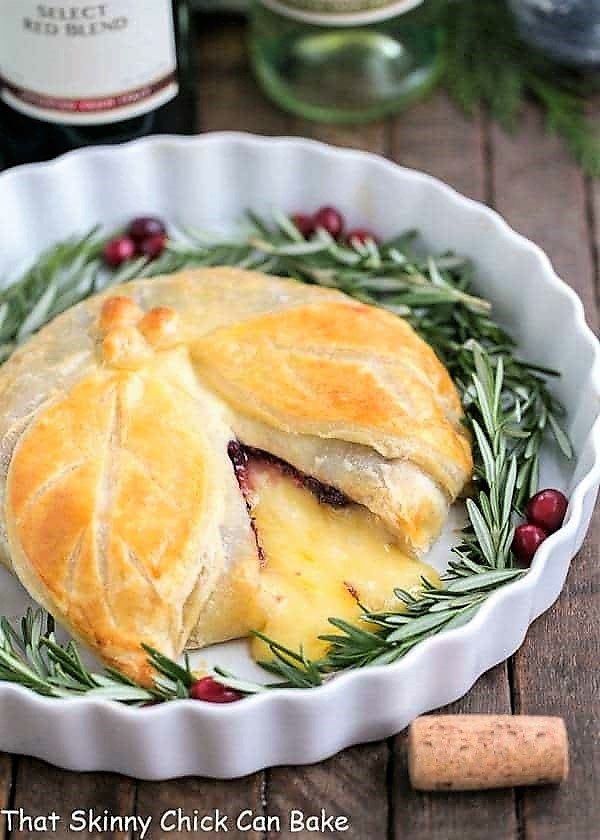 Cranberry Brie en Croute in a white ceramic dish garnished with rosemary and cranberries