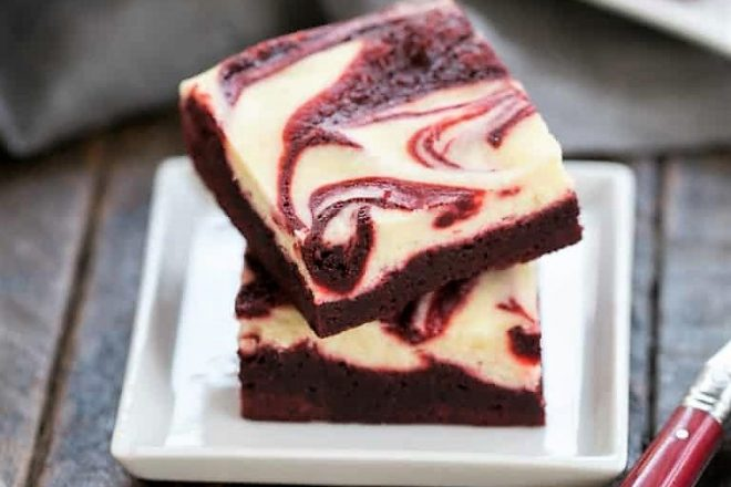 A stack of 2 red velvet cheesecake brownies on a square white plate