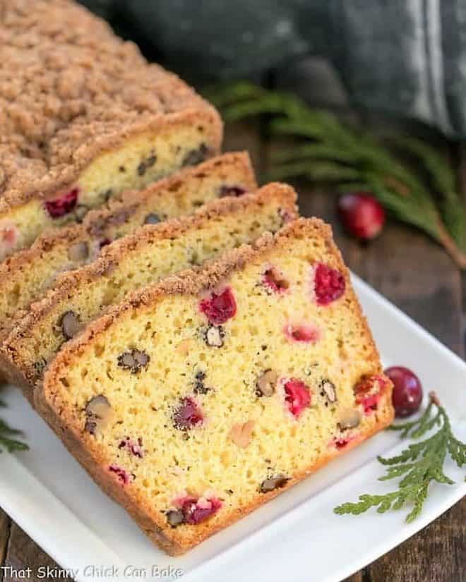 Streusel Topped Cranberry Orange Walnut Bread on a white ceramic tray garnished with fresh cranberries and cedar