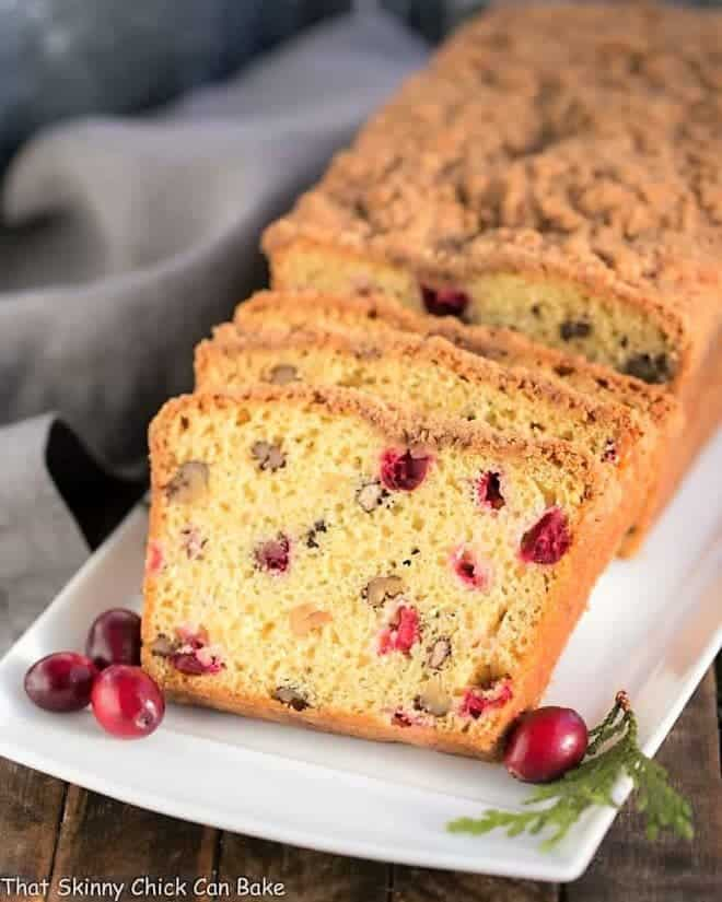 Streusel Topped Cranberry Orange Walnut Bread slices on a white platter