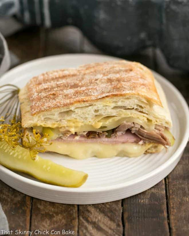 Ciabatta Cubano Sandwich Recipe on a round plate with a dill pickle