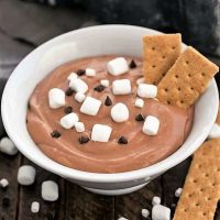 Easy S'mores Dessert Dip in a white bowl topped with mini marshmallows, chocolate chips and a couple graham crackers