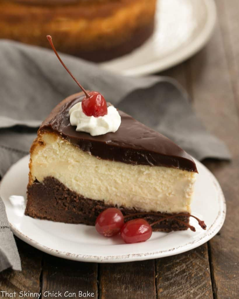 A slice of Hot Fudge Brownie Cheesecake on a dessert plate garnished with whipped cream and a cherry