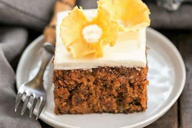 Slice of Old Fashioned Carrot Cake with Pineapple Flowers on a round white plate