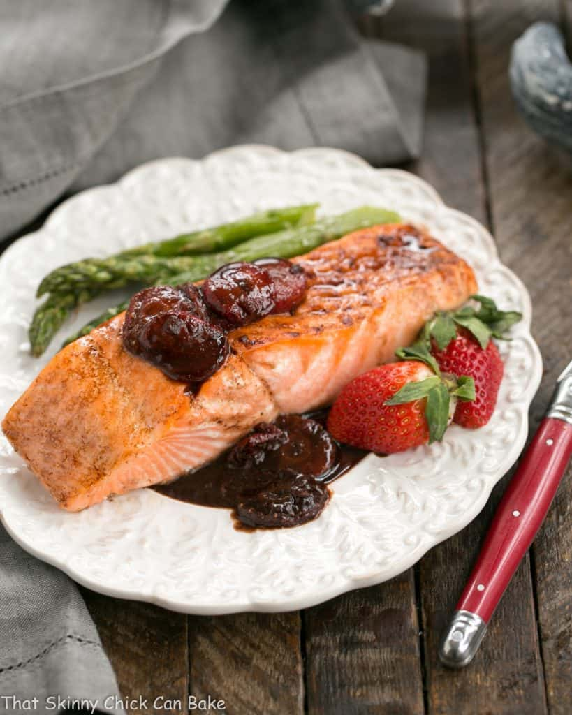 Strawberry Glazed Salmon on a dinner plate with asparagus and fresh strawberries