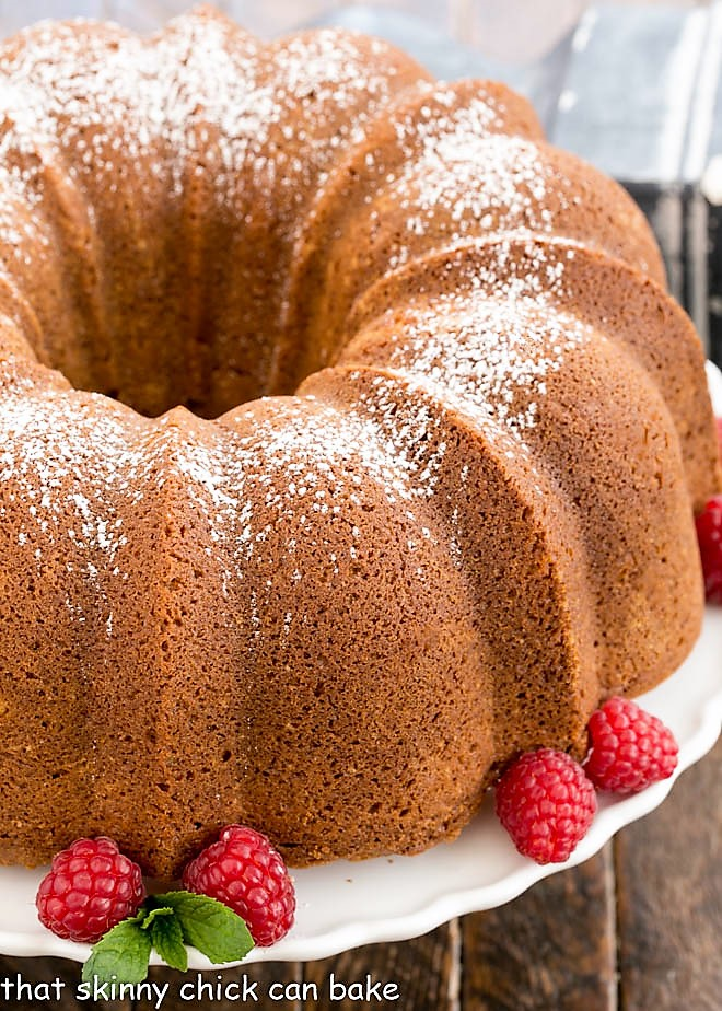 Close view of white chocolate Bundt Cake on a cake stand with raspberries and mint