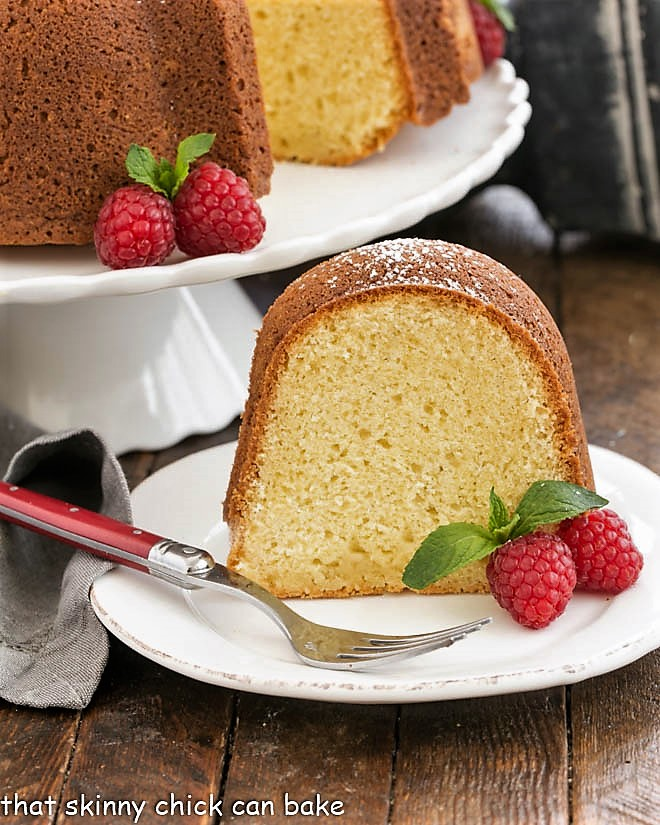 slice of white chocolate pound cake on a white plate with raspberries