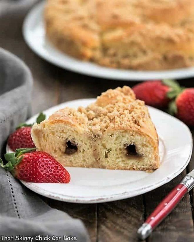 Slice of Streusel Coffee Cake Recipe on a white plate with strawberries