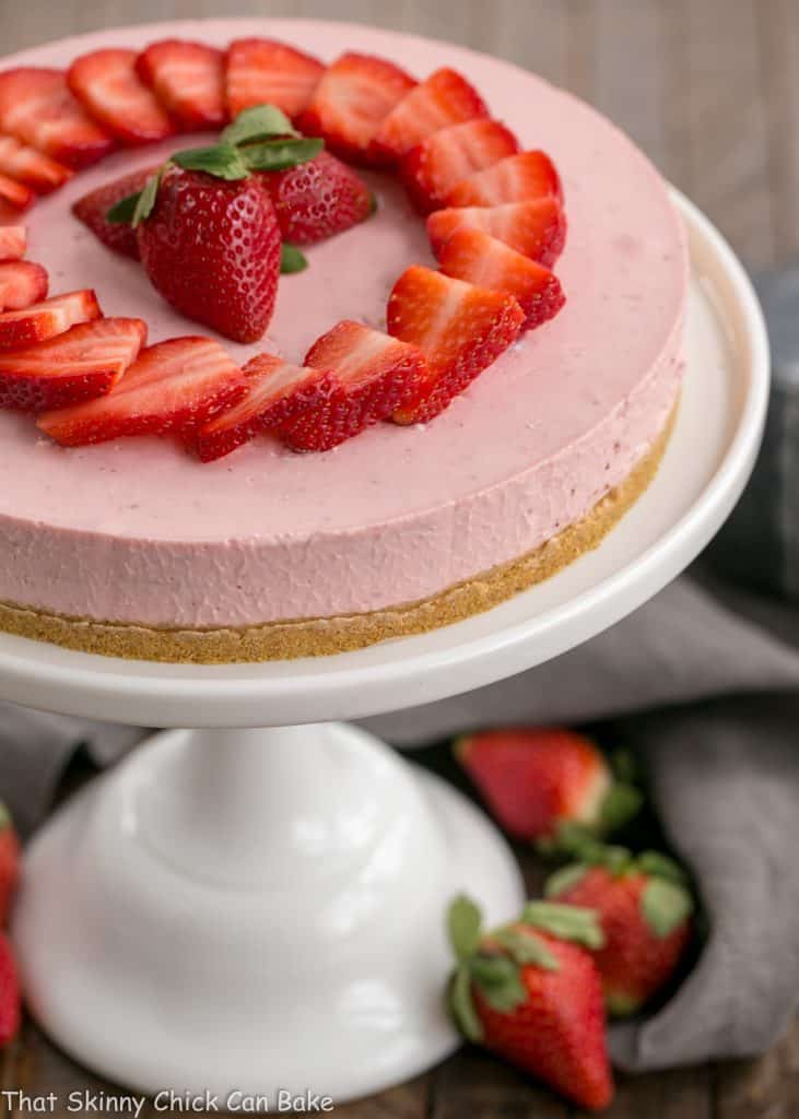 View of top of No-Bake Strawberry Cheesecake on a cake stand