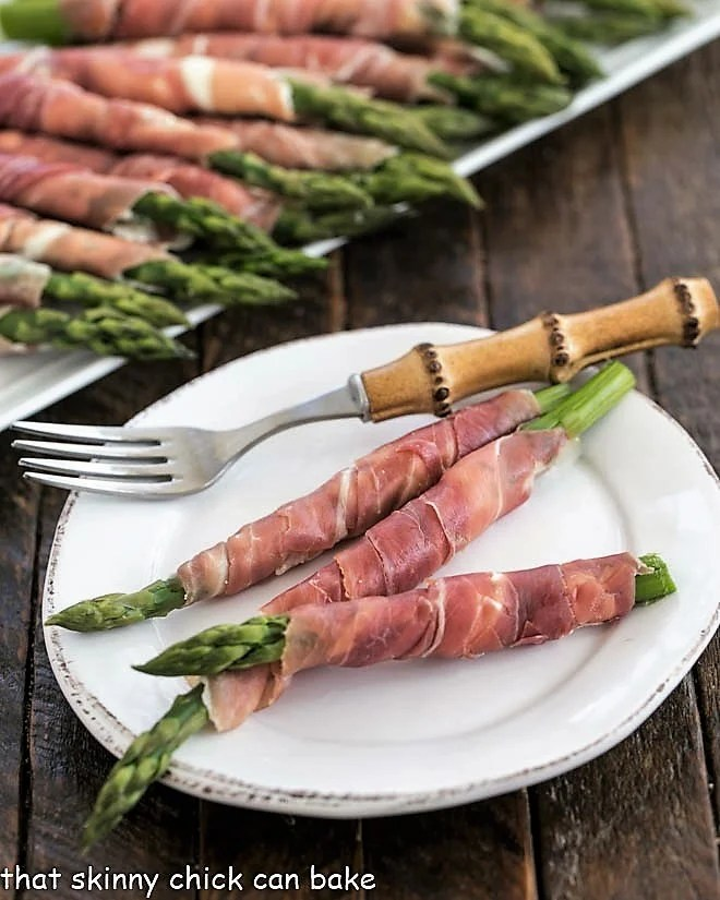 3 prosciutto wrapped asparagus spears on a white plate