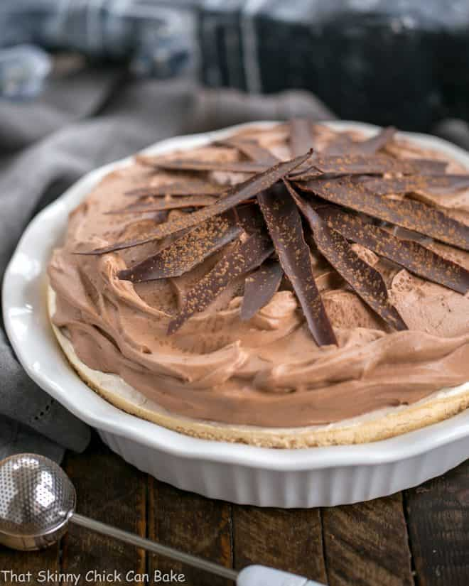 Chocolate Velvet Pie with Meringue Crust in white pie plate topped with chocolate shards and dusted with cocoa powder