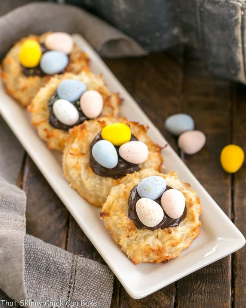 Coconut Macaroon Easter Nests lined up on a white ceramic tray