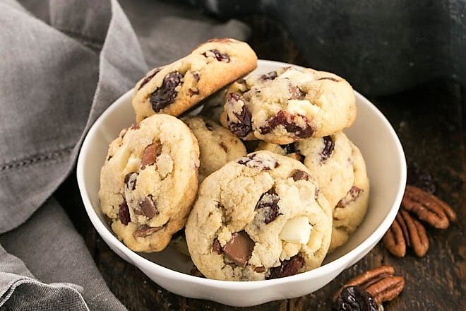 A white ceramic bowl filled with cherry chocolate chunk cookies