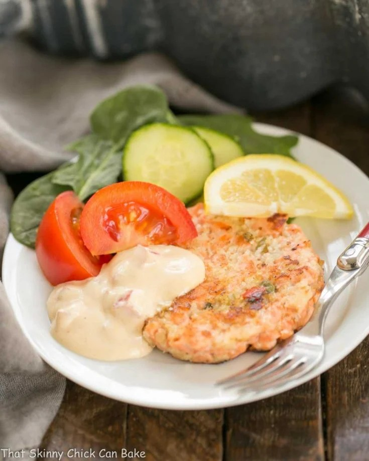 A white plate with a salmon cake, salad and remoulade sauce