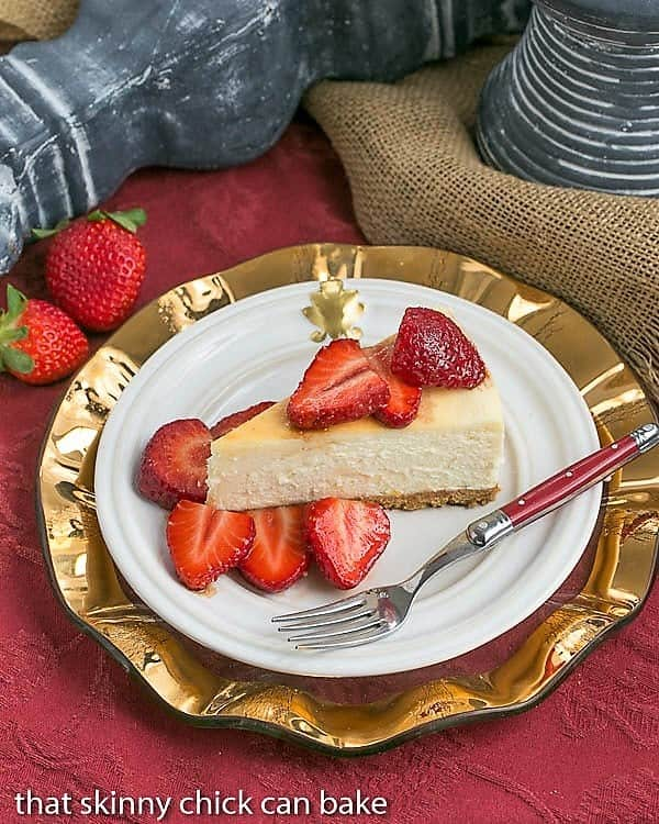 A slice of Mascarpone Cheesecake with Balsamic Strawberries on a white plate on top of a gold plate with a red handled fork