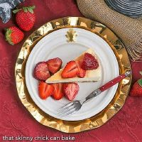 Italian Cheesecake with Balsamic Strawberries overhead view on a white plate over a gold charger plate