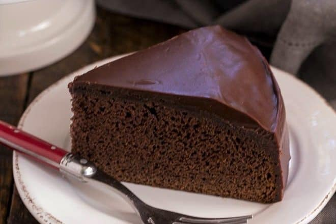 One Layer Chocolate Cake Recipe on a white cake with a red handled fork