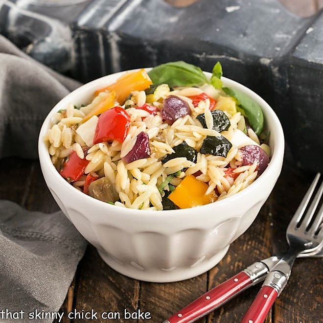 Small white bowl filled with orzo salad and two red handled forks