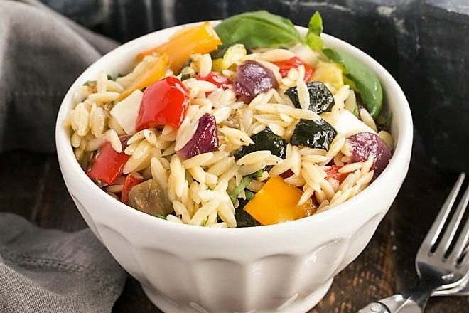 Orzo salad in a white bowl with 2 red handled forks