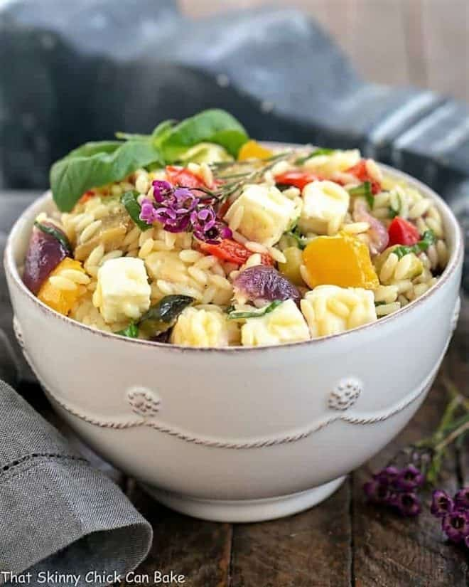 Roasted Vegetable Salad with Orzo, Mozzarella and Basil in a white bowl with a basil garnish