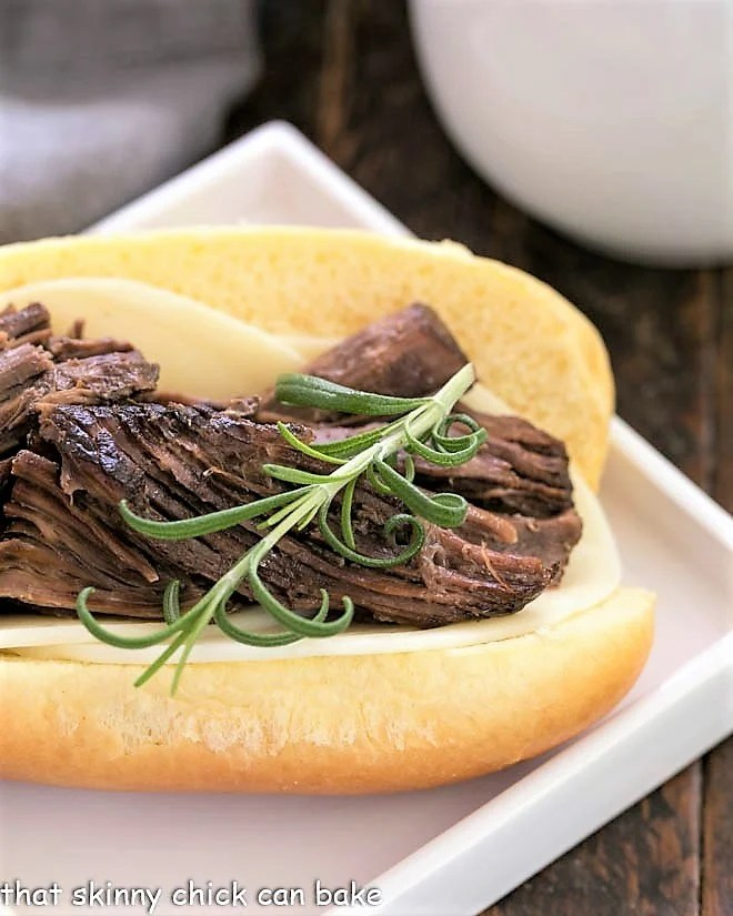 Close up of a French Dip sandwich topped with a sprig of fresh rosemary