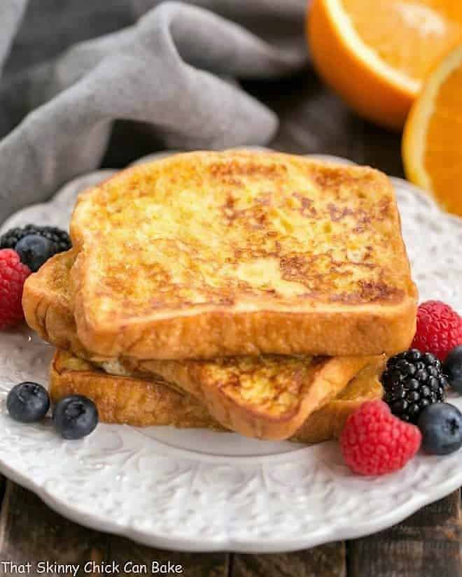 A stack of Grand Marnier French Toast on a white, decorative plate