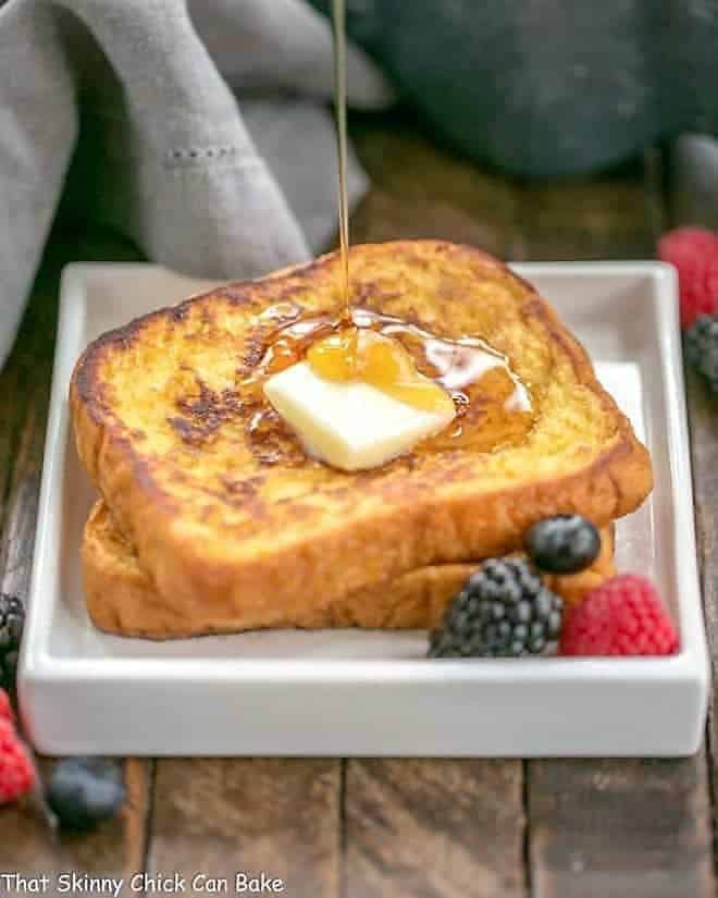 Grand Marnier French Toast on a square white plate with a stream of syrup pooling onto the surface