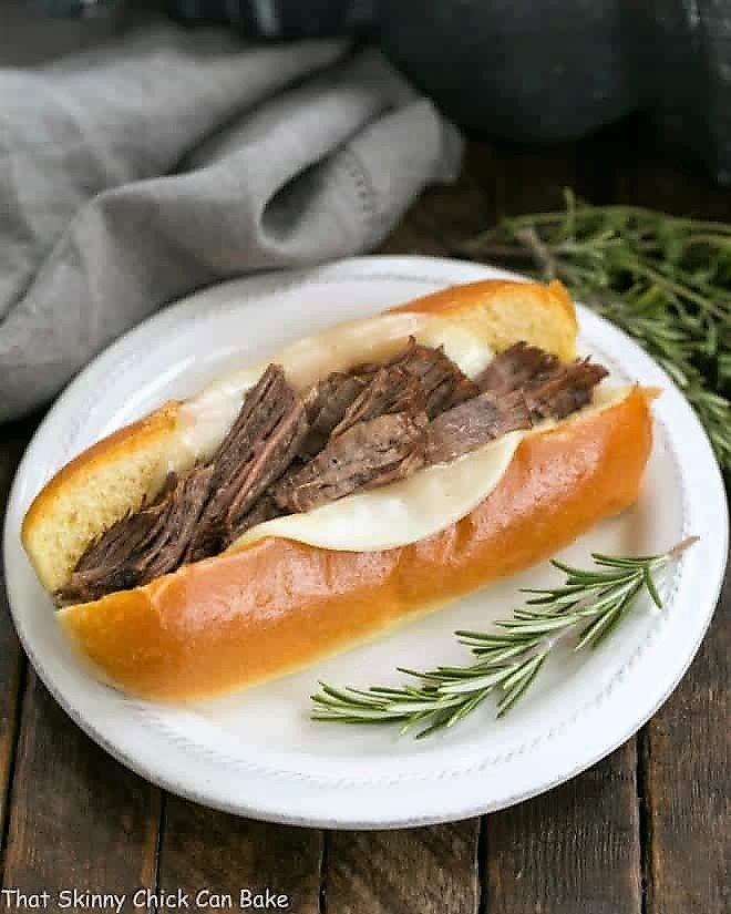 Instant Pot French Dip Sandwich on a white plate with a sprig of rosemary