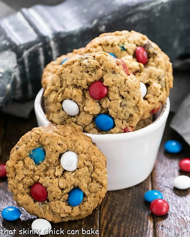 Peanut Butter Oatmeal Cookies with M&Ms in a small white bowl surrounded by patriotic colored M&Ms