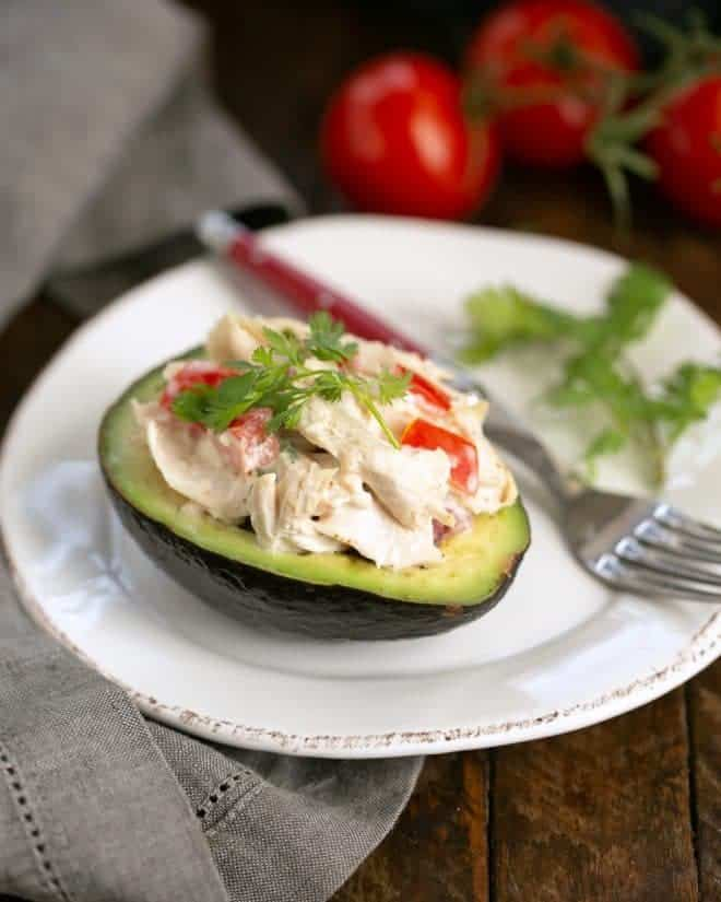 Southwestern Chicken Stuffed Avocado half on a white plate with a red handled fork