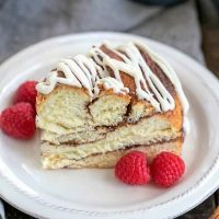 Cinnamon Twist Bread slice on a white plate with raspberries